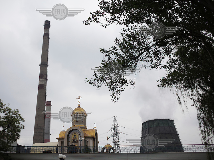 An Orthodox church stands next the chimneys at the Donetsk steel plant.
