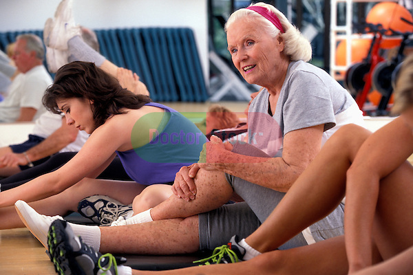 healthy elderly woman enjoying aerobic workout with younger adults in health club studio