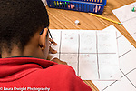 Education Elementary grade 3 back of male student's head as he works on math game created by students