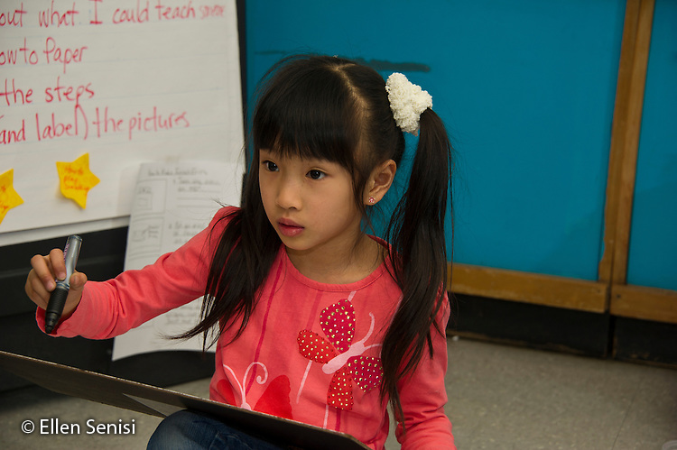 MR / Schenectady, New York. Paige Elementary School (urban public elementary school). First grade classroom. Student (girl, 6, Chinese American) listens in class and prepares to write on dry erase board. MR: Wil40. ID: AL-g1g. © Ellen B. Senisi.
