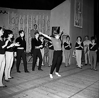 """Le 6 mai 1964. Vue d'ensemble des coullises sur scène du corps du ballet du Capitole entourant Annie Cordy, au centre, levant les bras pour montrer un mouvement de danse lors de la répétition de l'opérette """"Visa pour l'amour"""".<br /> <br /> <br /> PHOTO : André Cros"""