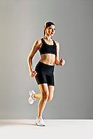 Young Caucasian woman running wearing black sports clothing