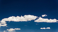 A blue sky is broken by a narrow band of white clouds.  Image includes room for text.  Cropped to 1920X1080, 16X9, HD aspect ratio.