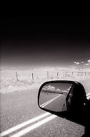 Desert road reflected in rear view mirror<br />