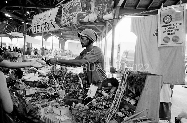 Detroit, Michigan<br /> USA<br /> July 24, 2010<br /> <br /> At Detroit's Saturday Eastern Market fresh food from farms in southeastern Michigan come to sell their produce. William Gardner, who has his own urban farm in Detroit proper with his wife Kelly, sells fresh food at the Grown-in-Detroit food stand. Grown-in-Detroit is a partnership with over 185 organizations and hundreds of individuals that support urban gardening and farming initiatives in Detroit, Hamtramck, and Highland Park.<br /> <br /> Urban gardening has taken Detroit by storm with so many vacant lots available after thousands of homes have been foreclosed, abandoned and demolished many residents and neighborhoods have turned those plots in to productive land.