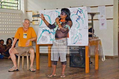 """Altamira, Brazil. """"Xingu Vivo Para Sempre"""" protest meeting about the proposed Belo Monte hydroeletric dam and other dams on the Xingu river and its tributaries. Indian camp at Bethania seminary. Kayapo translator and Prof. Seva explaining how the river will flood if the plans go ahead for the dams."""