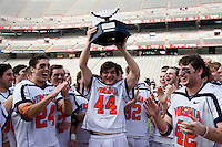 Virginia's Chris LaPierre (44) raises the tournament trophy next to teammates Ryan Nizolek (24) and Max Pomper (42) during the ACC men's lacrosse tournament finals in College Park, MD.  Virginia defeated Maryland, 10-6.
