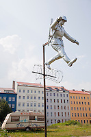 "Sculpture recreating the famous photograph of an East German border guard jumping to freedom over the Berlin Wall in its early days of construction when it was little more than a barbed wire fence. This is near the exact spot on Bernauer Strasse where the photo was taken and where many desperate scenes took place in 1961 as people jumped from the windows of their houses that stood on the edge of the Wall into West Germany. The green area is the former ""death strip"" that was created on the eastern side of the Wall once it was erected making it more difficult to escape to the West."
