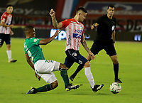 BARRANQUILLA - COLOMBIA, 17-02-2021: Juan David Rodriguez de Atletico Junior y Jhojan Valencia de Deportivo Cali disputan el balon, durante partido entre Atletico Junior y Deportivo Cali, de la fecha 7 por la Liga BetPlay DIMAYOR I 2021 jugado en el estadio Metropolitano Roberto Melendez de la ciudad de Barranquilla. / Juan David Rodriguez of Atletico Junior and Jhojan Valencia of Deportivo Cali battle for the ball, during a match between Atletico Junior and Deportivo Cali of the 7th date for BetPlay DIMAYOR I 2021 League played at the Metropolitano Roberto Melendez Stadium in Barranquilla city. / Photo: VizzorImage / Jairo Cassiani / Cont.