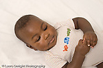 5 month old baby boy on back closeup looking at clasped hands horizontal African American