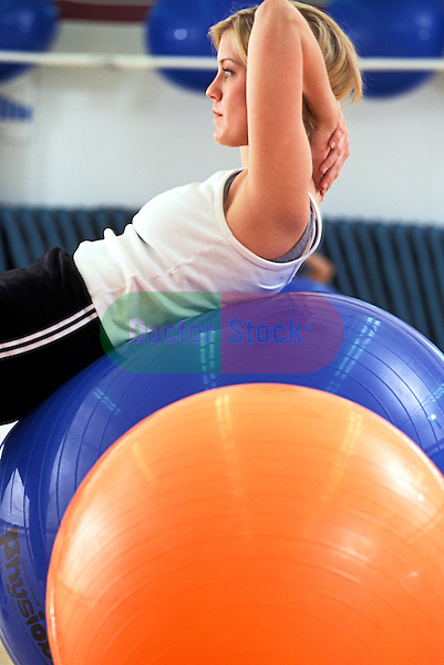 young woman does stretch exercise by balancing and rolling on large inflated ball