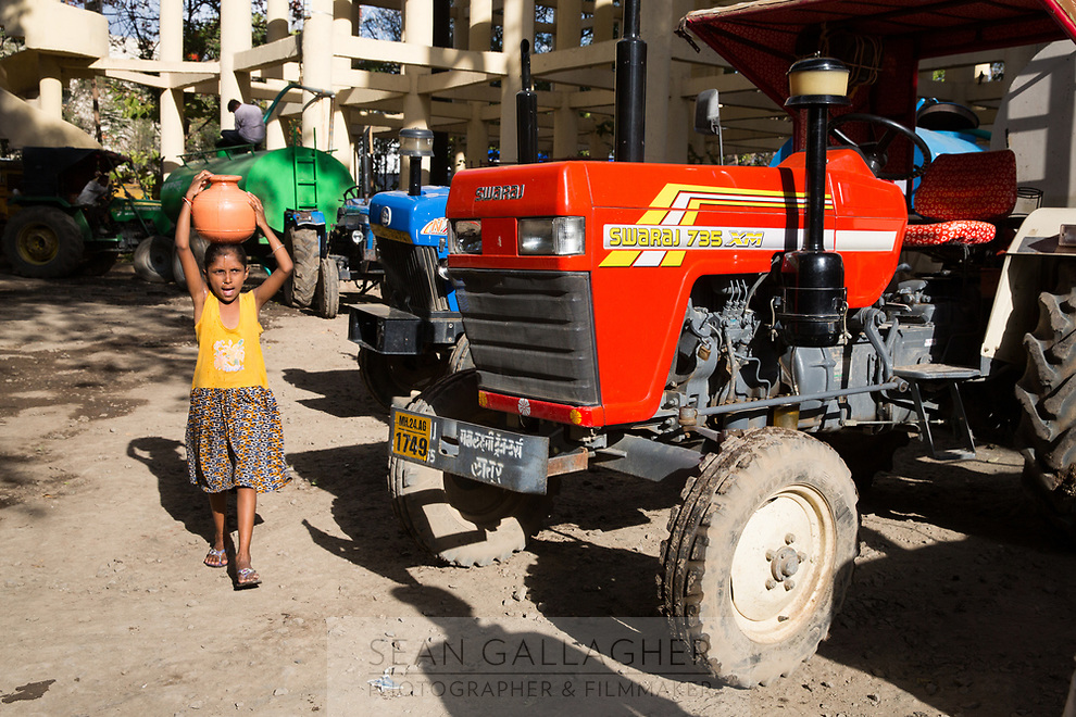 A young girl carries a water bottle near government water trucks which deliver water to Latur's residents. The trucks often run throughout the day and into the night however many communities do not receive enough water and are forced to travel to government water facilities to retrieve more water themselves.
