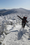 Winter hiker uses the Appalachian Trail to descend from the summit of South Twin Mountain in the White Mountains, New Hampshire USA during the winter months. Windy conditions cause snow to blow around.