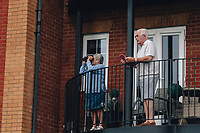 8th October 2021; AJ Bell Womens Cycling Tour, Stage 5, Colchester to Clacton on Sea.  A lady with binoculars watching the race with her husband from her balcony