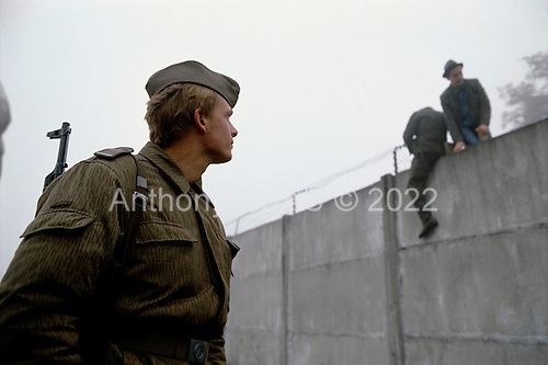 Lichterfelde, Berlin (West) and Teltow, Potsdam (East) crossing post, West Germany<br /> November 14, 1989 <br /> <br /> People watch as Germans cut wires to open the Berlin Wall. Germans gathered as the wall is dismantled and the East German government lifts travel and emigration restrictions to the West on November 9, 1989.