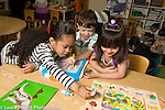 Education Preschool 4-5 year olds group of two girls and a boy working on puzzle
