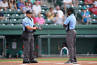 Umpires Ray Valero, left, and James Jean before a game between the Greensboro Grasshoppers and the Greenville Drive on Saturday, July 24, 2021, at Fluor Field at the West End in Greenville, South Carolina. (Tom Priddy/Four Seam Images)