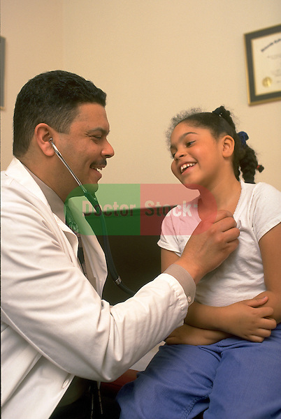 doctor examining chest of smiling young girl patient