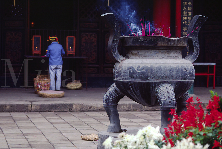 Worshippers of ethnic minority light INCENSE at the Buddhist YUANTONG TEMPLE in KUNMING - YUNNAN, CHINA