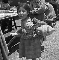 Kleines Mädchen mit Brüderchen auf dem Sonntagsmarkt in Pisao, Peru 1960er Jahre. Little girl and her toddlre brother joining the Sunday market at Pisao, Peru, 1960s.