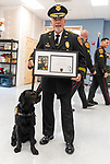 WOLCOTT, CT 072921JS17 Wolcott Police Chief Edward Stephens poses with Mallard, the Wolcott Police Department's therapy dog and a framed photo and certificate following a swearing in ceremony for Mallard Thursday at the Rietdyke Senior Center in Wolcott. <br /> Jim Shannon Republican American