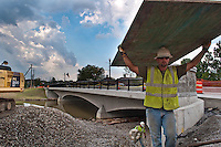 Worker carries a sheet of plywood used for a concrete form at the main Street Bridge construction site. The plywood was being removed as part of the cleanup of the site as construction nears completion.