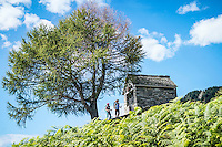 The Via Alta Verzasca is a five day ridge traverse hike above the Valle Verzasca in the Ticino region of Switzerland. The hikers are stopped to look at a small chapel.