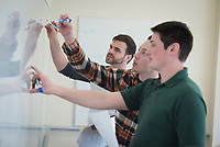 Kyle Wilson, left, Austin Pavlas, center, and Michael Dunn, right, work on problems at the white board as engineering students review for finals in the Mixsell-Piccard Family Collaboration and Learning Center in UAA's Engineering and Industry Building.