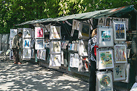 Book stalls of Les Bouquinistes selling books and art prints on Quai de Montebello on the left bank of the Seine River in Paris, France.