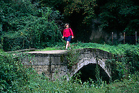 Hiker crosses a bridge in the countryside of   TUSCANY, ITALY