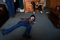 """Dressed as a cowboy, Sheriff Tanner Lauman is """"shot dead"""" on the living room floor in a moment of play.<br /> <br /> Kitty Lauman trains mustangs--as she says working with the horses, not against them.  They have a ranch in Prineville, OR.<br /> <br /> Kitty, her husband Rick and their children, Josie, 2 ½,  and Tanner, 5,  ride mustangs. Kitty Lauman started her career as a horse trainer at the tender age of nine, under the guidance of her grandfather, John Sharp. <br /> <br /> She later became a top Pee Wee and High School Rodeo contestant, competing in barrel racing and cutting, among other events. Despite her mother's assertion that """"horse training isn't a real job,"""" Kitty managed to make a living as a trainer after high school (and her mom now helps out with the business!) <br /> <br /> Kitty won the title of Miss Rodeo Oregon in 1994, and since then, has continued to expand her horse training knowledge and experience.  She placed second in the Extreme Mustang Makeover, a national competition in 2008."""
