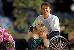 man in wheelchair holding pet dog
