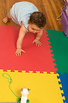 9 month old baby girl crawling onto play mat to reach toy