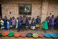 School collecting water in buckets during rain storm. Kyondo, Rakai, Uganda, Africa.