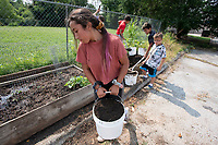 Angelina Virto, 12 carries dirt in a bucket Monday July 19, 2021 while working with other children to make garden beds during the Lifesource Summer Program. The project is spearheaded by program director Betty Metcalf. Metcalf also teaches at Butterfield Elementary School in Fayetteville and manages a garden project there. Visit nwaonline.com/21000720Daily/ and nwadg.com/photo. (NWA Democrat-Gazette/J.T. Wampler)