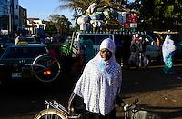 BURKINA FASO, capital Ouagadougou, muslim woman with headscarf / muslimische Frau mit Kopftuch und Plastikbeute mit Trinkwasser im Mund