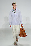 Model walks runway in a 4 pocket Havana shirt, ecru stripe como trouser from the Palmiers du Mal Spring Summer 2017 collection by Brandon Capps and Shane Fonner, with A.M. Club palm leaf silk scarf and Moore & Giles x Richard Haines Benedict weekender, at Skylight Clarkson Square on July 14 2016, during New York Fashion Week Men's Spring Summer 2017.