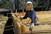 Female carpenter building foundation forms. Labor, traditional male role, construction, building, safety, safety equipment, tools, work. female carpenter. Mt. Shasta CA USA construction site.