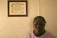 Canadaville, LA--Dwan Green in her new home, next to the only posession she was able to salvage from her destroyed home in the 9th Ward of New Orleans - her daughter's high school diploma. Liam Maloney / Special to The Gazette
