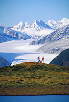 Hikers admire the Mendenhall Glacier, Juneau, Alaska from their perch atop Thunder Mountain in the Tongass National Forest (Southeast Alaska). An alpine pond is in the foreground. Juneau Alaska, Thunder Mountain, Tongass National Forest.