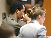 Sniper suspect John Allen Muhammad, left, puts his head in his hand as he listens to the testimony of Reverend Albert Archer, as his attorney Christie Leary looks on during court proceedings in Virginia Beach Circuit Court in Virginia Beach, Virginia on November 7, 2003. <br /> Credit: Tracy Woodward - Pool via CNP
