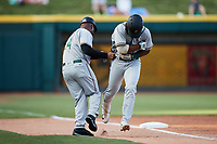 Greensboro Grasshoppers manager Kieran Mattison (24) fakes a hand-off to Matthew Fraizer (14) as he rounds third base after hitting a home run against the Winston-Salem Dash at Truist Stadium on June 15, 2021 in Winston-Salem, North Carolina. (Brian Westerholt/Four Seam Images)