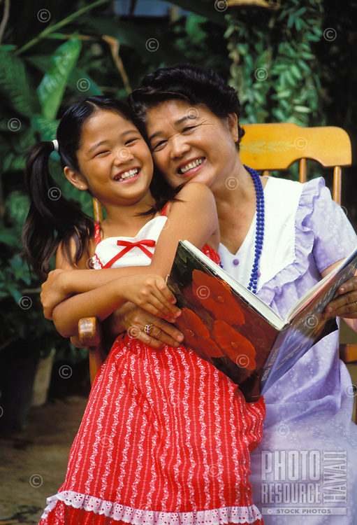 Local grandmother and granddaughter enjoy reading a book together.