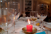 Empty wineglasses on a Christmas table dressed with a burning candle.