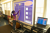 MR / Schenectady, NY. Zoller Elementary School (urban public school). Kindergarten inclusion classroom. Student (girl, 5) signs herself in for the day on digital whiteboard set up with attendance taking software. MR: Stu1. ID: AM-gKw. © Ellen B. Senisi.