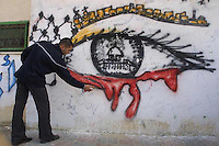 Amar Abed draws a graffiti of a crying eye looking at the AL Aqsa mosque in Jerusalem with a view of the city atop of bleeding eye, in the streets of Khan Yunis, in the Gaza Strip. Photo by Quique Kierszenbaum