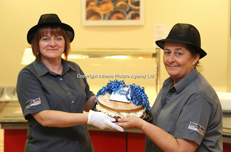 Pictured L-R: Lotto winners colleagues Andrea Davies and Clare Birchall holding a cake for them at Neath Port Talbot hospital. Wednesday 08 November 2017<br />Re: Presentation of hospital catering syndicate win £25m in Euromillions Jackpot at Hensol Castle, south Wales, UK. Julie Saunders, 56, Doreen Thompson, 56, Louise Ward, 37, Jean Cairns, 73, SIan Jones, 54 and Julie Amphlett, 50 all work as catering staff for Neath Port Talbot Hospital in south Wales.
