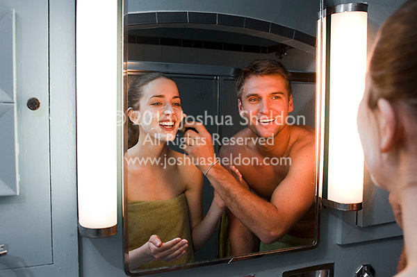 Reflection of young couple playing around in bathroom mirror