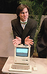"""Steven Jobs, chairman of the board of Apple Computer, leans on the new """"Macintosh"""" personal comptuer following a shareholder's meeting Jan. 24, 1984 in Cupertino, Ca.  The Macintosh, priced at $2,495, is challenfing IBM in the personal computer market. (AP Photo/Paul Sakuma)"""