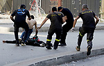 Men run to rescue a person shot while preparing to fire a rocket-propelled grenade, amidst clashes in the area of Tayouneh, in the southern suburb of the capital Beirut, on October 14, 2021. - Gunfire killed several people and wounded 20 at a Beirut rally organised by the Shiite Hezbollah and Amal movements to demand the dismissal of the Beirut blast lead investigator, the state-run National News Agency said. Photo by Marwan Bou Haidar